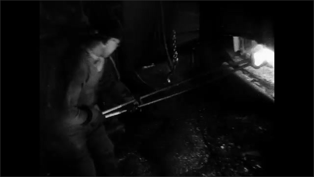 1930s: Objects move along conveyor belt, man sprays objects. Gloved hand holds wrench. Man guides hooks around pole, pulls hot metal out of fire, inserts it into machine. Machine smashes on metal.