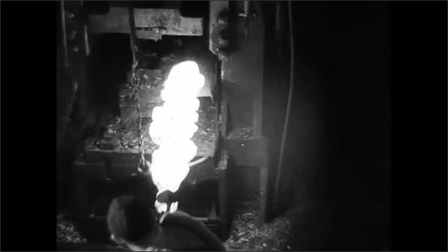 1930s: Man turns and moves hot metal as machine smashes down on it and man sprays water at it. Man removes hot metal from molding machine, inserts in into other machine, machine smashes it.
