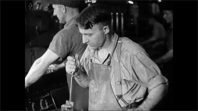 1930s: Men remove engine blocks, place them on conveyor belts. Man places gauge down into metal cylinders.