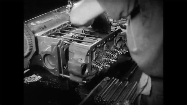 1930s: Men assemble engine parts.