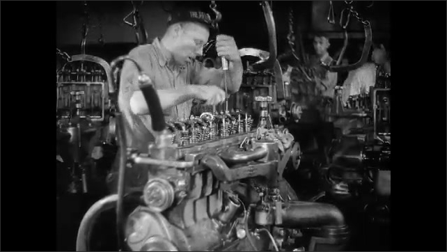 1930s: Engine blocks hang from chains, move around factory on tracks. Man assembles engine. Man holds rod to ear, listens to engine parts moving.