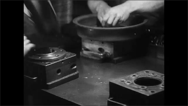 1930s: men in hats stand at table, pass around and assemble metal rims with square and circle parts near overhead assembly line. hands run curved steel items through mechanical punch to rivet plate.