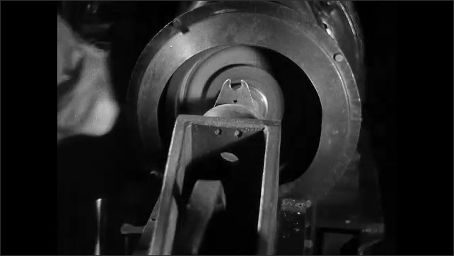 1930s: hands secure curved metal to pattern board and clears holes. worker puts steel clamp on rod, guides into machine with lever and pulls product out as assembly line runs nearby,
