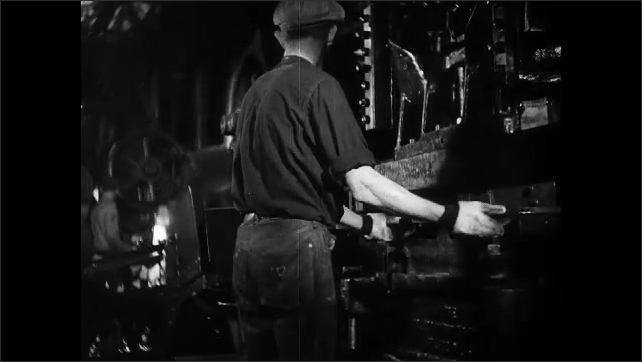 1930s: man swivels part in machine, releases grip, removes circle and places new element in tool. worker places sheet of steel in cutter, wheel forms and rolls down assembly line at factory.