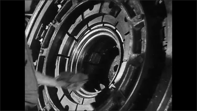 1930s: steel wheel spins inside machine with rollers until hand in glove pulls cylinder out and into round metal press. man slides sheet into machinery. palm presses large button in factory.