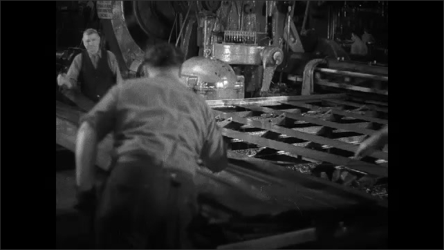 1930s: hand holds handle. man stands at machine and observes process in factory. men in hats and gloves hit and spread sheets of metal with hammers on assembly line conveyor belt.