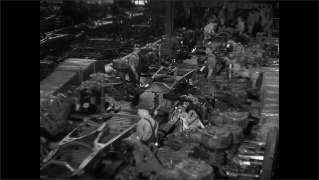 1930s: men in overalls work on automobile chassis going down assembly line as retractable mechanical arms brace steel items in Chevrolet car factory. hand pulls lever near controls.