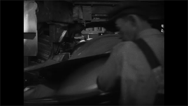 1930s: men press buttons on control panel near machinery. workers in overalls fit car hood inside press machine, wait for weight to stamp down and pull off extra metal parts in Chevrolet factory.