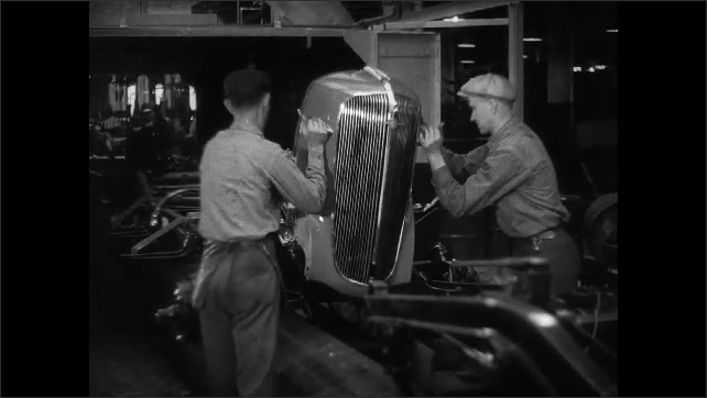 1930s: hands rub roof of car and chalk a zero on metal. men attach front grill to car chassis on assembly line. worker places running board and fender on conveyor belt in Chevrolet factory.