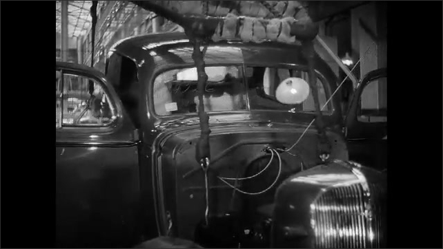 1930s: crane lowers body of 1936 Chevrolet coupe onto assembly line as men open doors, disconnect hoist and connect auto parts to chassis in Chevy automotive factory.