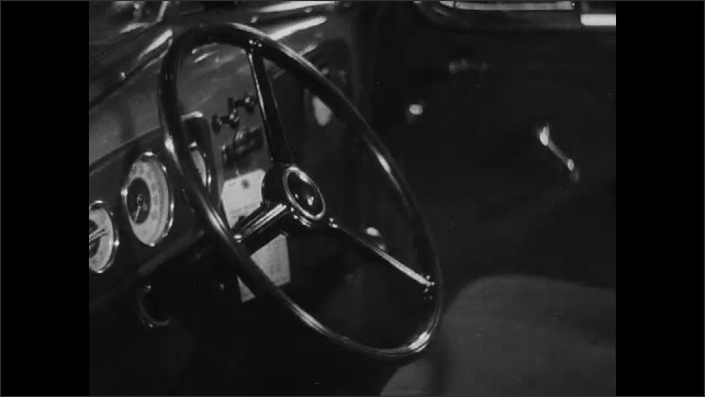 1930s: clean fresh seats shine inside the interior of a 1936 Chevrolet sedan as man appears in driver's seat, hands grip the steering wheel and front door shuts with window down.