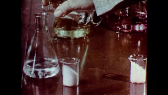 1960s: UNITED STATES: glass beakers shaken by hand. Chemical change inside beaker