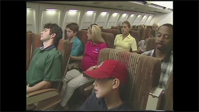 1990s: Airplane in sky.  Woman speaks to young man in cabin.