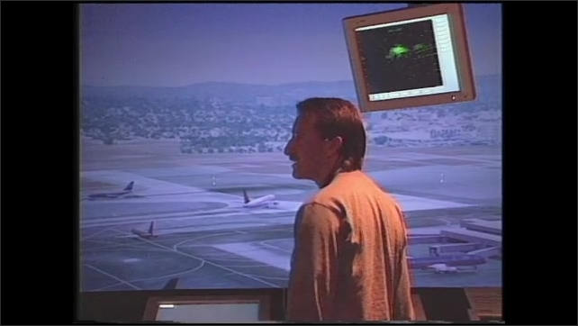1990s: Man works on computer.  People talk in air traffic control simulation room.