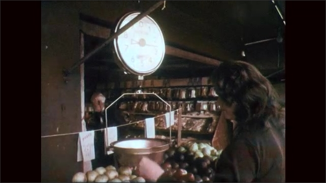 1970s: Woman puts fruit in scale. Hand picks up apples, tilt up, woman puts apples in scale. Close up of scale. Hand puts apples in scale. Low angle shot, truck pulls up to curb.
