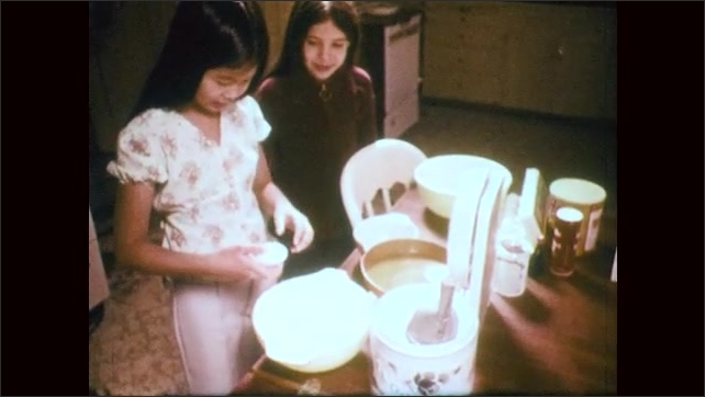 1970s: Feet on scale. Close up of gauge on scale. Girls at table, girl cracking egg. Hands separate egg, pan to close up of girl. Hand pour egg into bowl.