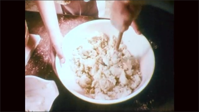 1970s: Close up, milk pours into measuring cup. Hands mix dough, tilt up to girl. Close up of girl. Hands mix liquid in bowl. Close up of girls.