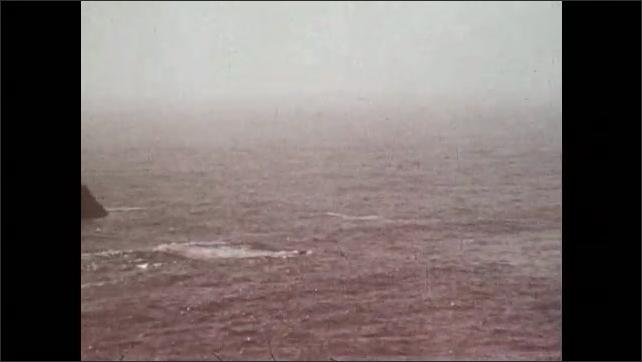 1970s: Waves in the ocean. Rocks and coastline.