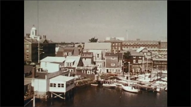 1970s: Light flashes across computer screen. Buildings with docks, boats at docks. Boat full of horseshoe crabs.