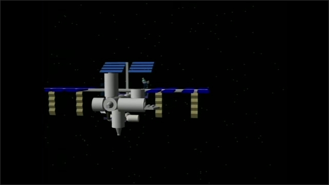 """2000s: Title credit """"Meet Me at the Station"""" appears over computer rendering of space station. Animated robot appears floating in front of the space station, smiling and talking."""