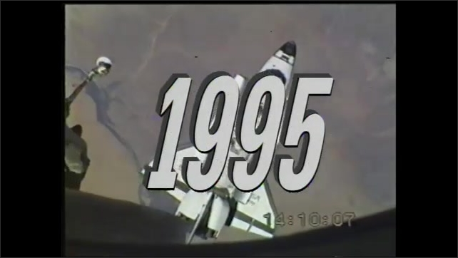 2000s: Clip from Space Station in 1986. Space shuttle hooks up to the space station in 1995. Russian and American astronauts shake hands on the space station.