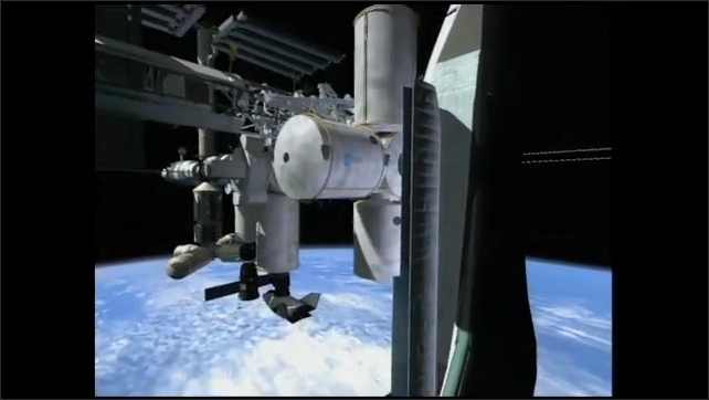 2000s: Animated robot M-C perches on a table and talks. Computer rendering of the space station. Footage of an astronaut floating through the hallways of the space station.