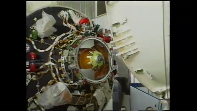 2000s: Control module of space station Zarya Sunrise being constructed in Russia. Cables and wiring inside of the control module. Rocket taking off from ground in flames.