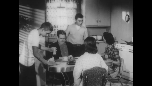 1950s: UNITED STATES: boy stands up from table. Boy spills drink. Family eat meal together. Boy arrives at house. Friend visits house.