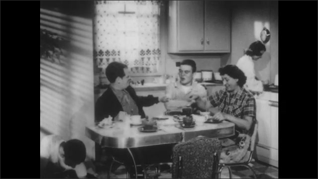 1950s: UNITED STATES: boy sits at table. Family eats meal together. Parents eat with teenagers