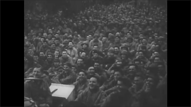 1950s: UNITED STATES: soldiers cross land. Audience watch show. Injured man in wheelchair claps. Soldiers fire weapons. Soldiers land on beach. Forces entertainment. Bombs fall from plane