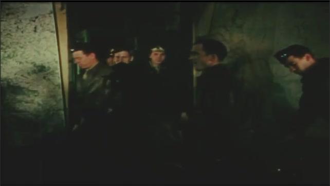 1940s: Hands insert firing pin into bomb. Men enter room, sit down. Screen raises, man enters, talks in front of chalkboard. Men sitting in line.