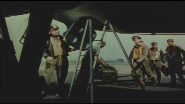 1940s: Men in flight gear. Men talk in front of plane. Men in gear. Men climb into plane. Man moves plane part.