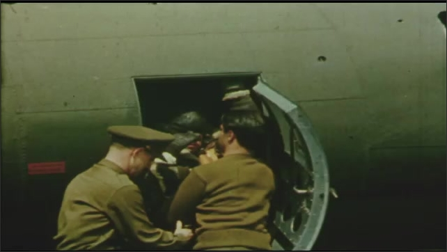 1940s: UNITED STATES: soldier with head wound on plane. Medical team take pilots from plane. Man on stretcher