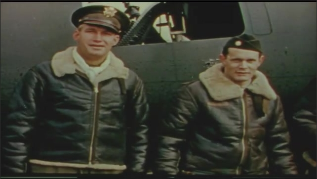 1940s: UNITED STATES: plane after on board fire. Crew smile by damaged plane after battle. Man in uniform smiles. Man claps hands