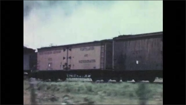 1940s: Workers stand in cotton field watching machine harvest cotton. Machine harvests cotton. Train speeds down tracks. Engine on locomotive turns.