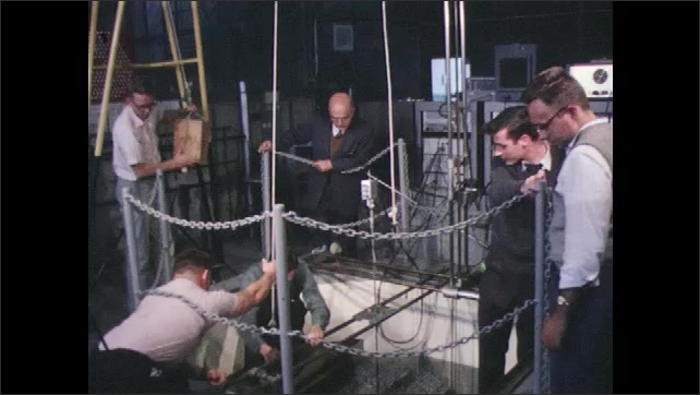 Group of men pull ropes and lift rods from liquid tank in floor of plant. Men pull ropes and adjust counter weights on pulleys. Man lifts rods with hook and lowers it into water.