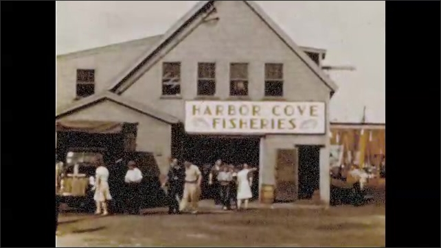 1940s: Cars and pedestrians move along crowded city street. Man walks on sidewalk. People walk from Harbor Coast Fisheries. People and families walk on crowded city sidewalk.