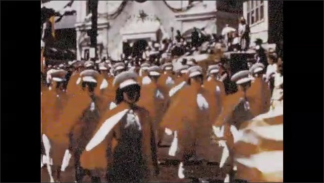 1940s: Soldiers in uniform march through city streets in parade. Men carry statue of Saint Peter in parade.