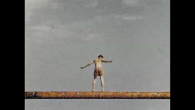 1940s: Men race row boats on harbor. Man balances on greased pole. Men watch festivities from fishing boats. Men balance on and fall from greased pole into harbor.