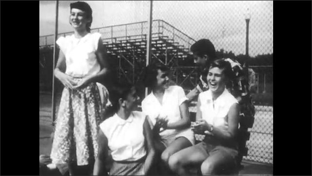 1950s: Teenagers watching tennis match cheer and jump. Teens watching match talk happily.