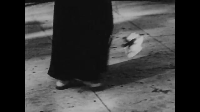 1940s: UNITED STATES: hand picks up flower from ground. Shadow over flower. Lady walks along street. Shadow of lady on wall