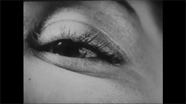 1940s: UNITED STATES: close up of mascara on eye. Lady sits in chair. Lady puts flower on lap. Lady runs hand up body.