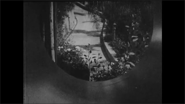 1940s: UNITED STATES: view of path from house. Eye closes. Make up on eye. Lady walks along path.