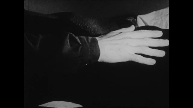 1940s: UNITED STATES: man leans over lady. Man runs hand along woman's body. Close up of woman's lips. Close up of eye. Lady watches man.