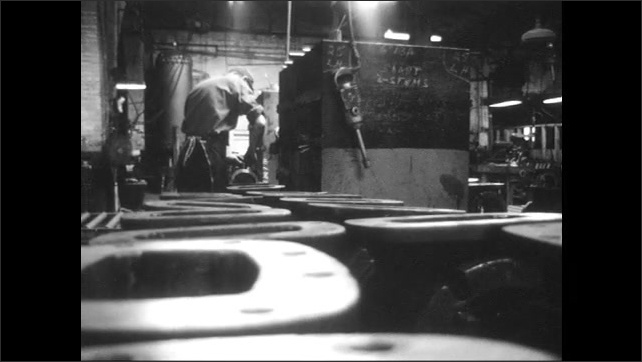 1960s: Machine moves while water falls on it. Worker stacks metal products in a factory. Worker moves two products made of metal on the ground. Hands fit screws into a metal product.