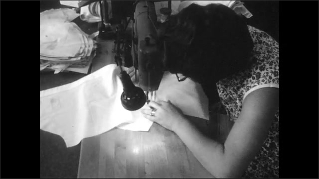 1960s: Woman sits at a sewing machine and puts a small fabric over another and sews them. Hand takes a button from a container and holds fabric into the machine that sews buttons on the fabric.