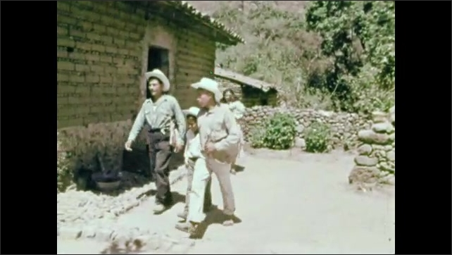 1950s: baby lays on woven mat with blanket and pillow. man with mustache and boys wear hats, exit house, grab ropes on mules and lead them away.