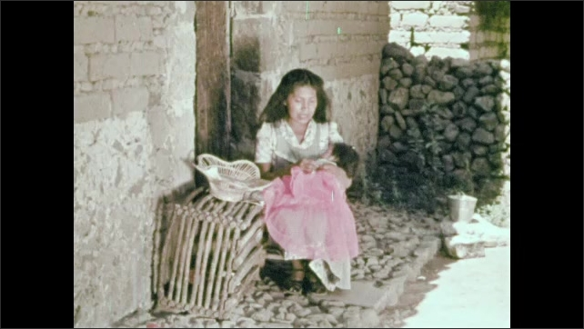 1950s: woman with apron sits on chair, sews on cloth, holds baby and sings lullaby near house in yard. mother washes clothes on rock next to stream.