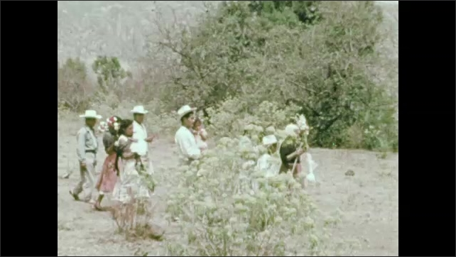 1950s: boy in hat stares. men, women, girls and boys rise from benches, gather and walk. Old woman carries flowers as people follow down road, across field and up trail. steps rise on Aztec pyramid.