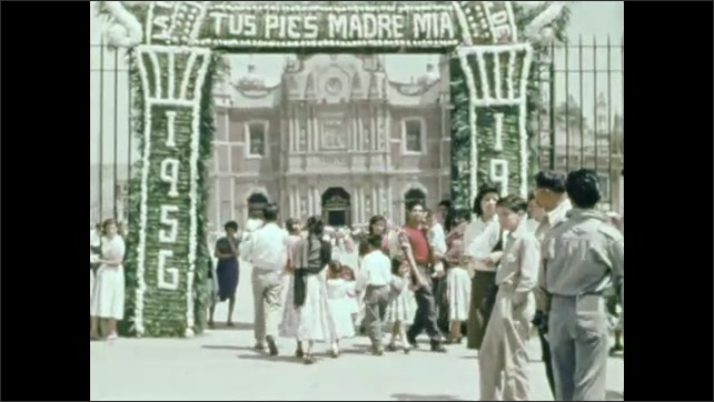 1950s: boy stares at Great Green Warriors statues at entrance of Mexico City. Men, Women, Girls and Boys pass the gates of Guadalupe decorated for 1956. Crowds gather in plaza before basilica.